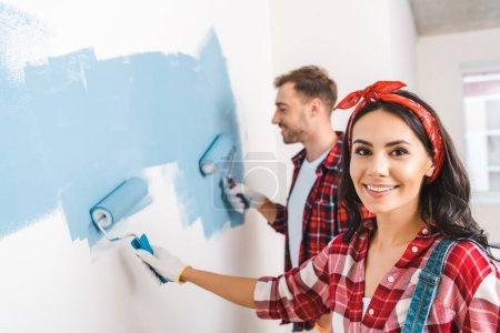 Photo pour Mise au point sélective de jolie femme tenant le rouleau près du mur peinture homme - image libre de droit
