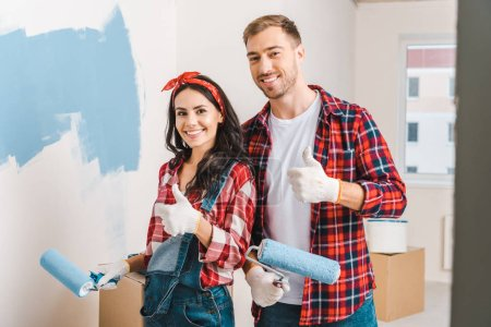 Photo for Cheerful man and woman showing thumbs up while holding rollers in hands - Royalty Free Image