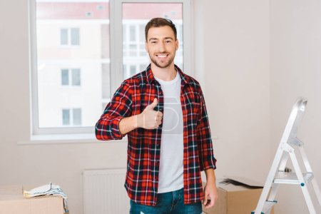 Photo for Cheerful man showing thumb up while standing at home - Royalty Free Image