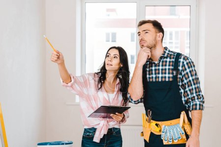 attractive woman holding clipboard and pointing with finger near handyman