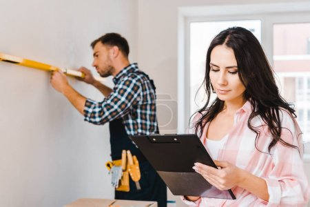 Photo for Selective focus of attractive woman holding clipboard with handyman measuring wall on background - Royalty Free Image