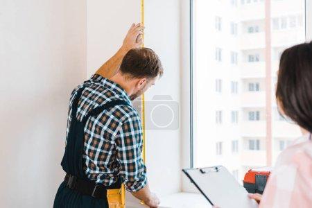 Photo pour Mise au point sélective de bricoleur mesurant la fenêtre près de clientes - image libre de droit