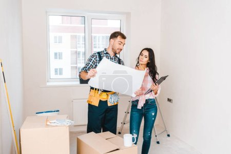 Photo for Cheerful handyman holding blueprint near attractive client - Royalty Free Image