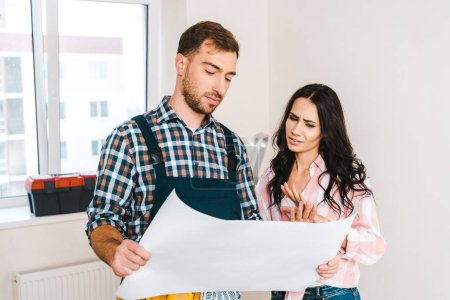 Photo for Handsome handyman holding blueprint near attractive client - Royalty Free Image