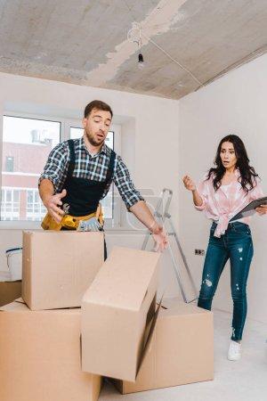 Foto de Sorprendido mujer mirando caer caja cerca guapo handyman - Imagen libre de derechos