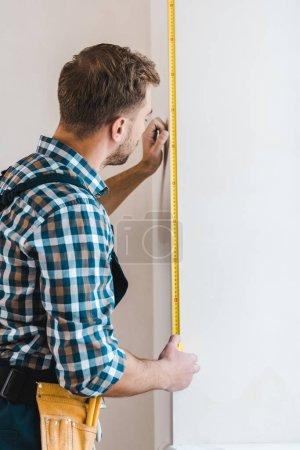 Photo pour Bricoleur debout et mur de mesure avec ruban à mesurer - image libre de droit