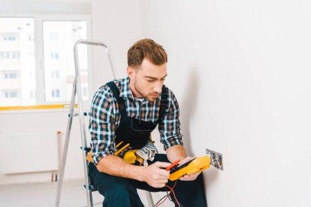 Photo for Handsome handyman holding digital multimeter while sitting near power socket - Royalty Free Image