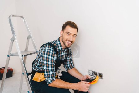 Photo for Cheerful handyman holding digital multimeter and sitting near power socket - Royalty Free Image