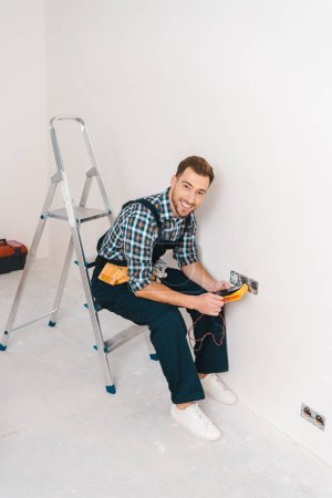 Photo for Happy handyman holding digital multimeter and sitting on ladder near power socket - Royalty Free Image