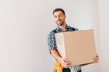 Photo for Happy handyman holding box while standing near wall - Royalty Free Image