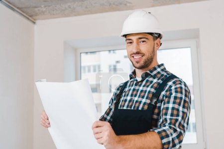 Photo for Cheerful handyman smiling while holding blueprint - Royalty Free Image