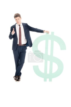 Photo for Successful young businessman with big dollar sign pointing at you isolated on white - Royalty Free Image