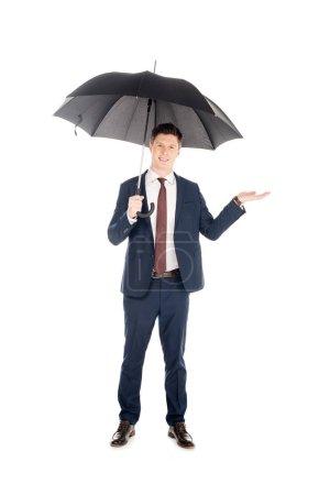 Photo pour Homme d'affaires souriant en costume avec parapluie vérifiant la pluie, isolé sur blanc - image libre de droit