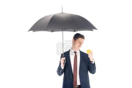 Photo pour Souriant le jeune homme d'affaires avec parapluie regardant tirelire isolé sur blanc - image libre de droit