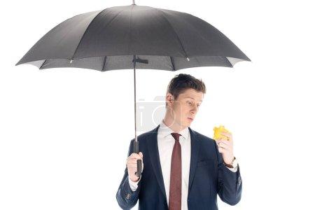 Jungunternehmer mit Regenschirm blickt auf Sparschwein isoliert auf weißem Grund