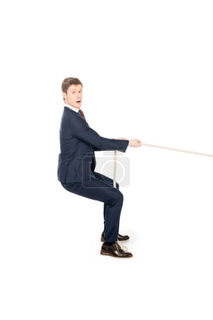 Photo for Young shocked businessman pulling rope isolated on white - Royalty Free Image