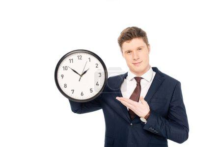bel homme d'affaires tenant horloge isolé sur blanc