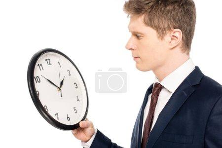 beau homme d'affaires regardant horloge isolé sur blanc