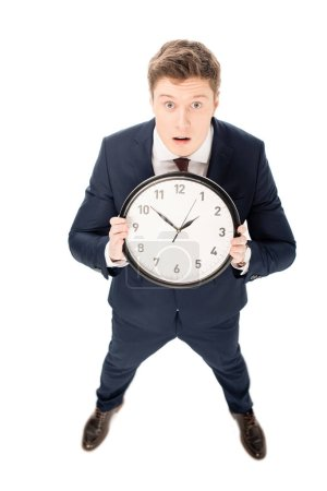 Photo for Shocked handsome businessman holding clock isolated on white - Royalty Free Image