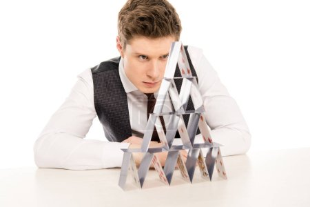 focused man making pyramid from playing cards isolated on white