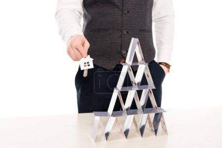 Photo pour Recadrée vue d'agence immobilière détenant les clés de la maison et en montrant la pyramide de cartes à jouer, isolé sur blanc - image libre de droit