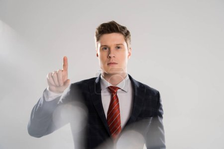 selective focus of young businessman pointing on grey