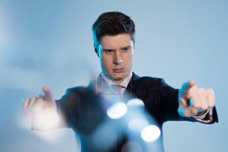 Foto de Enfoque selectivo del empresario serio tocar algo con los dos dedos en azul - Imagen libre de derechos