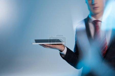 Photo pour Foyer sélectif de jeune homme d'affaires tenant dispositif numérique sur bleu - image libre de droit