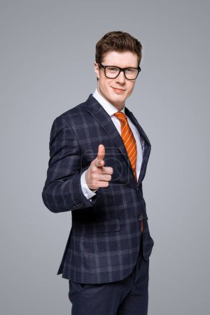 Photo for Successful stylish businessman smiling and pointing at you isolated on grey - Royalty Free Image