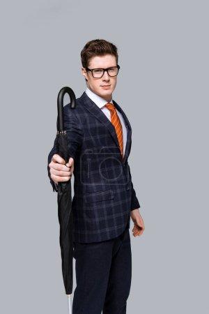 Photo pour Prise de vue studio d'homme d'affaires élégant posant avec parapluie isolé sur fond gris - image libre de droit