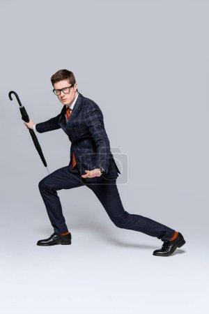 Photo for Stylish businessman have fun with umbrella on grey - Royalty Free Image