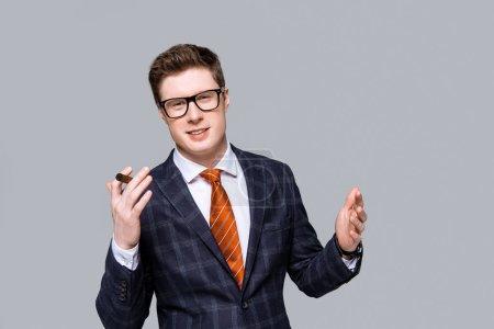 Photo pour Succès élégant beau homme d'affaires avec cigare isolé sur gris - image libre de droit