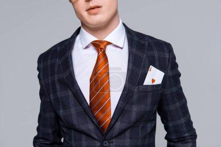 Photo pour Vue recadrée d'homme d'affaires élégant avec as en poche isolée sur fond gris - image libre de droit