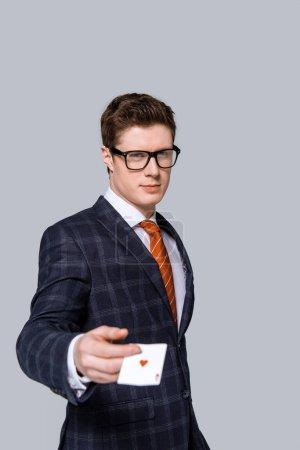 Photo pour Homme d'affaires élégant détenant la carte à jouer isolé sur fond gris - image libre de droit