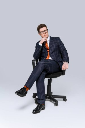 Photo for Stylish thoughtful businessman sitting on chair on grey - Royalty Free Image