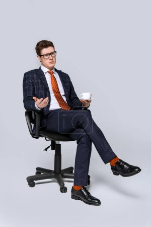 Photo for Stylish businessman sitting on chair with cup of coffee on grey - Royalty Free Image