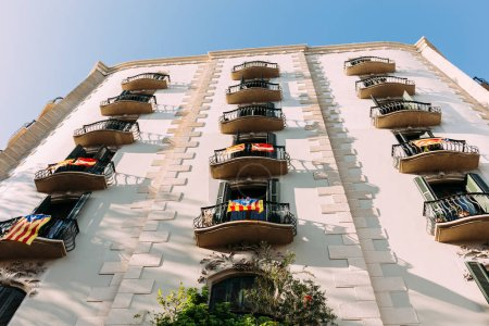 white house with balconies with national flags, barcelona, spain