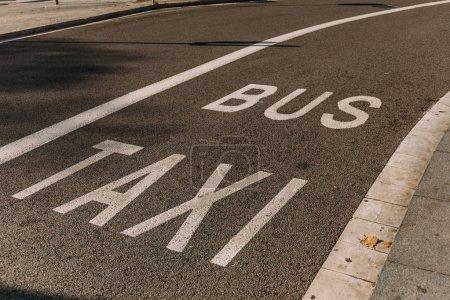 Photo pour Chaussée d'asphalte avec des marques blanches, inscriptions «bus» et «taxi», Barcelone, Espagne - image libre de droit