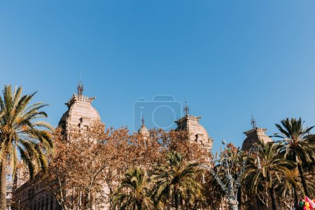 old building with towers behind green trees, barcelona, spain