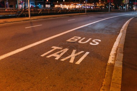 """asphalt roadway with white markings, """"bus"""" and """"taxi"""" inscriptions, barcelona, spain"""