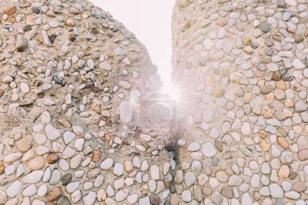 Multicolored handwork stone walls on bright sunlig...