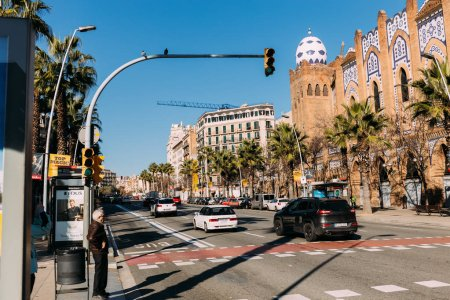 BARCELONA, SPAIN - DECEMBER 28, 2018: busy street with old multicolored building and cars moving on wide road