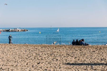 BARCELONA, SPAIN - DECEMBER 28, 2018: scenic view of sea and people sitting on beach