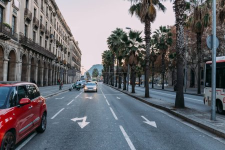 Photo for BARCELONA, SPAIN - DECEMBER 28, 2018: busy street with buildings, palm trees, and cars moving on roadway - Royalty Free Image