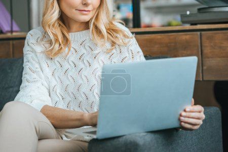 cropped view of woman with blonde hair using laptop at home