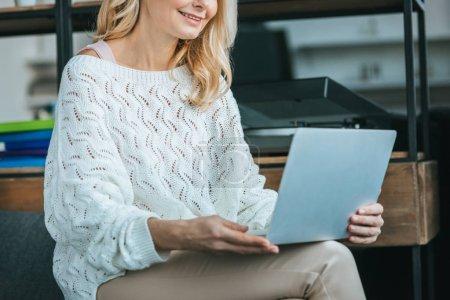 Photo pour Vue recadrée femme heureuse souriant tout en regardant ordinateur portable à la maison - image libre de droit