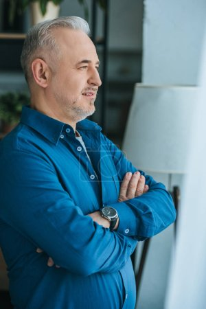 Photo for Handsome man standing with crossed arms at home - Royalty Free Image