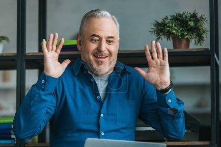 Photo pour Homme gai érigeant mains et souriant à la maison - image libre de droit