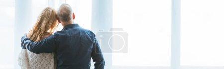 Photo pour Vue arrière du couple debout et étreignant près de la fenêtre à la maison - image libre de droit
