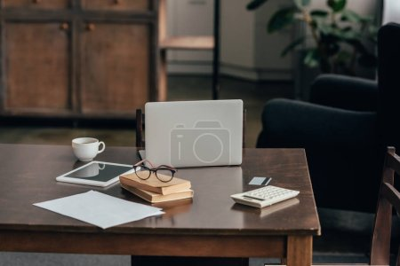 Photo for Gadgets near cup, books and calculator on desk - Royalty Free Image